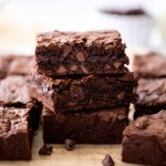 one bowl fudge brownies stacked on parchment paper