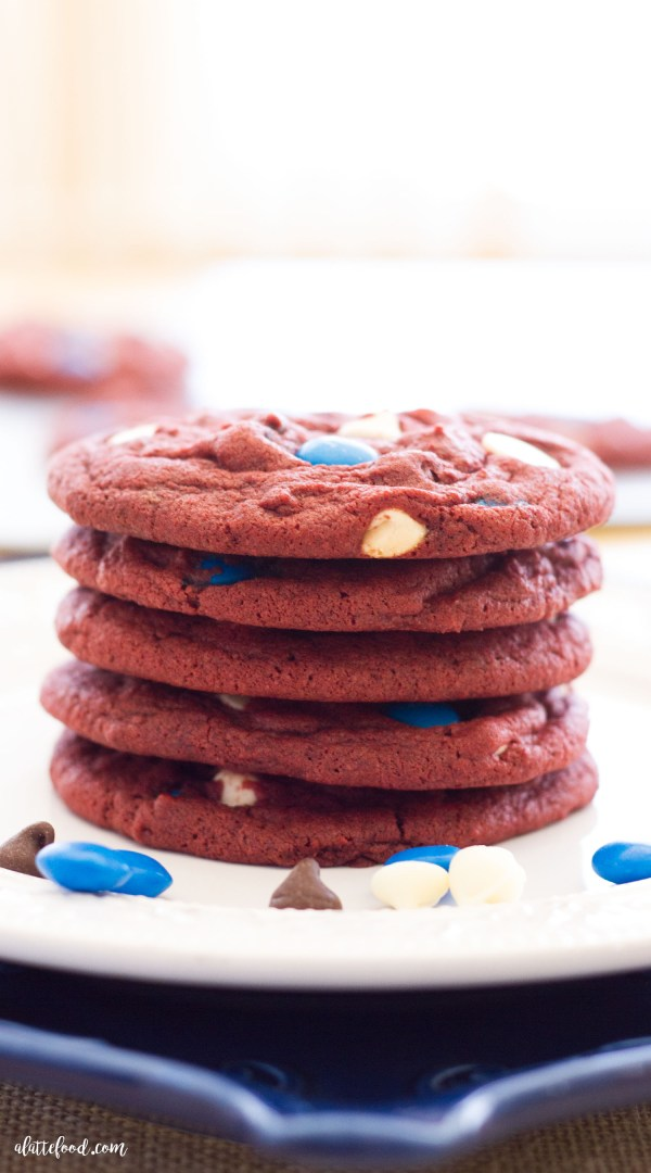 These homemade red velvet cookies are chocolatey, chewy, and intensely red! Mixed with white chocolate chips, semi-sweet chips, and blue M&Ms, these delicious cookies are the perfect addition to your 4th of July party!