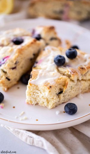 Lemon Glazed Blueberry Scones on plate with a bite missing