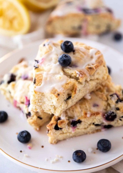 Three lemon blueberry scones on white plate stacked with one scone missing a bite