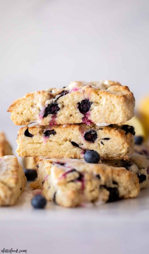 fresh blueberry lemon scones stacked on parchment paper