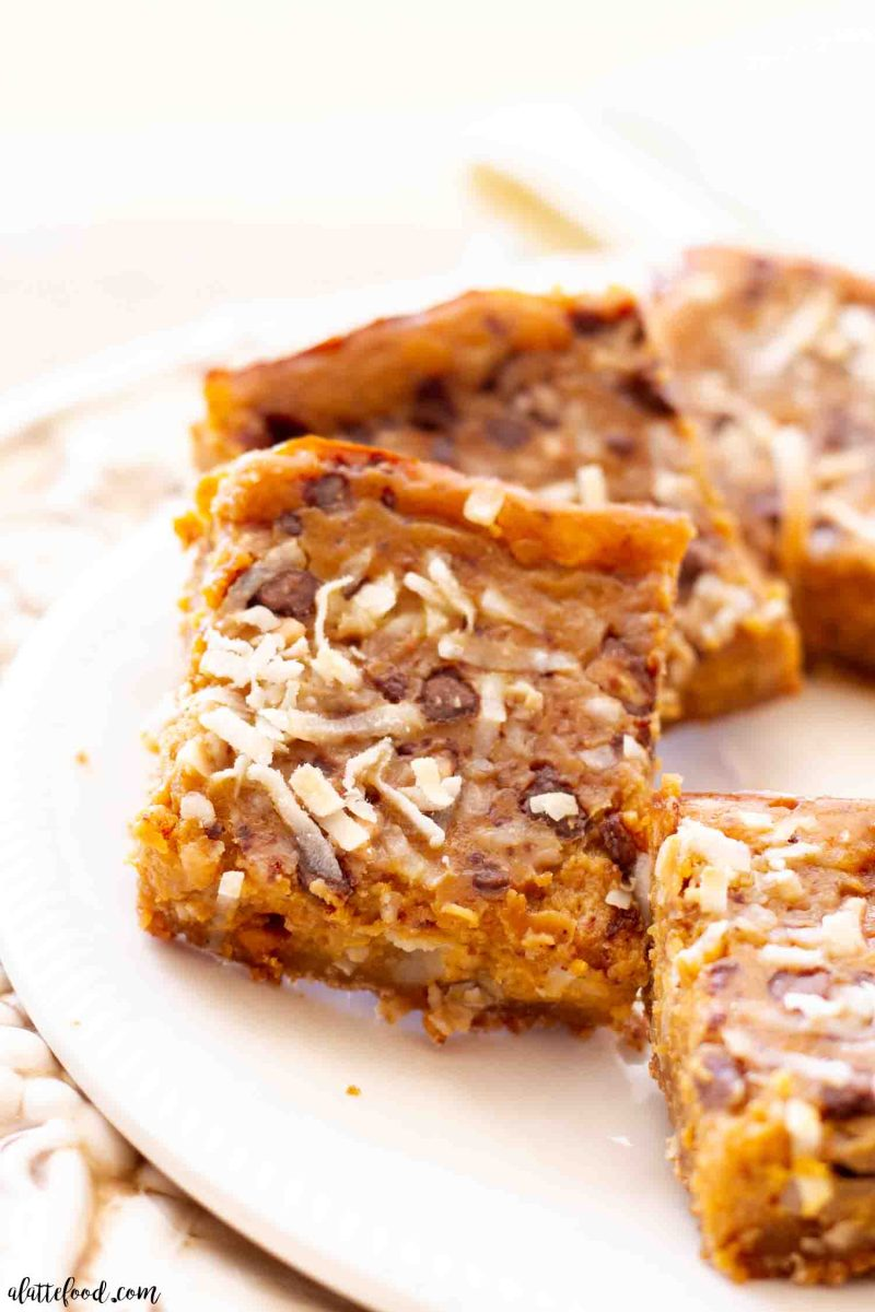 baked pumpkin seven layer bars with a graham cracker crust on white serving dish