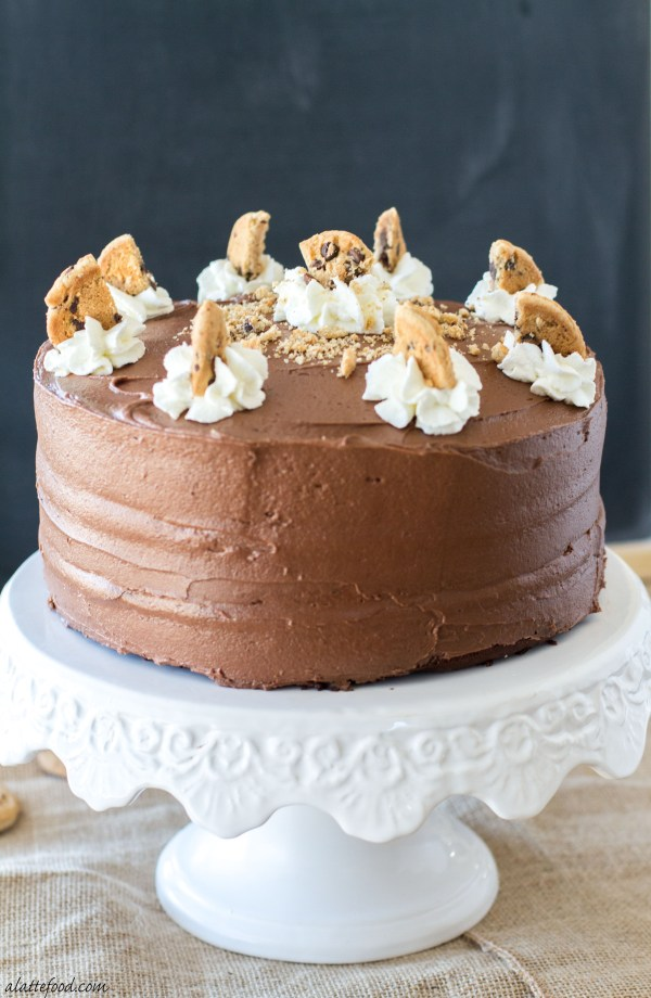 This delicious cake has chocolate cake and chocolate chip cookie layers, is filled with Nutella and whipped cream, and topped with creamy chocolate frosting and crushed chocolate chip cookies. | www.alattefood.com