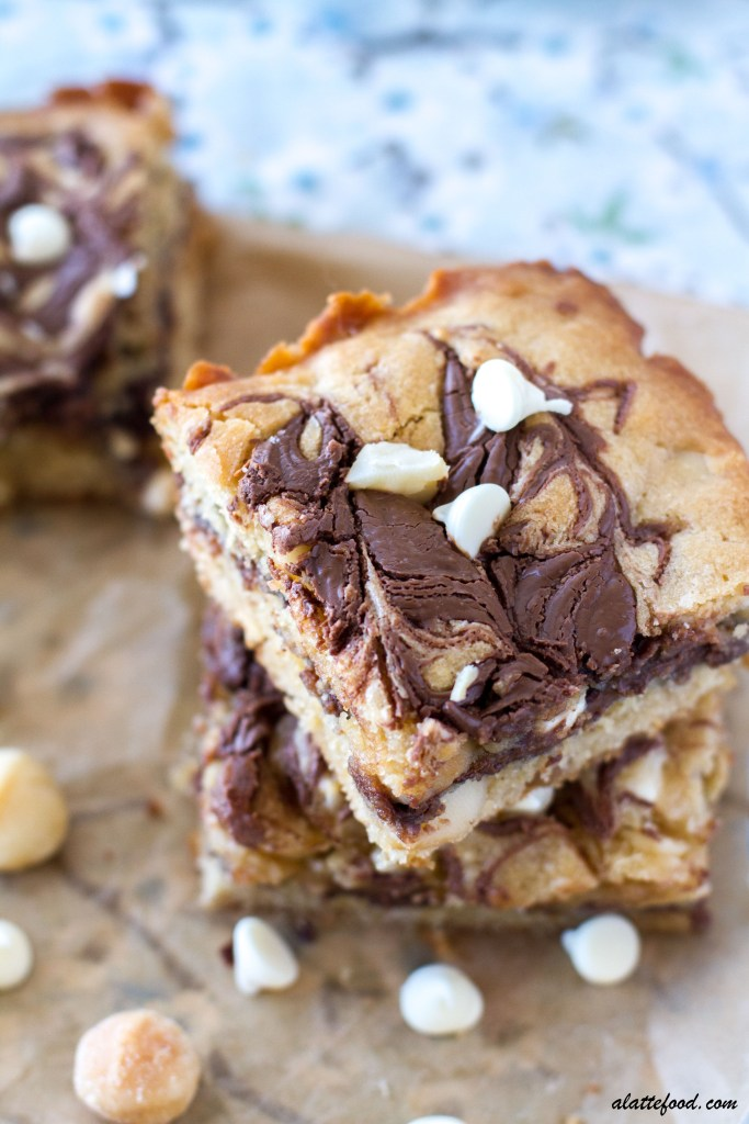 These indulgently rich Nutella White Chocolate Macadamia Nut Bars have a gooey Nutella center!   These Nutella gooey bars are like a White Chocolate Macadamia Nut Cookie met a Nutella Cookie Bar to create an irresistible dessert bar! These gooey Nutella bars are the life of the party. With all of the white chocolate chips, macadamia nuts, and swirls of Nutella, how could they not be?