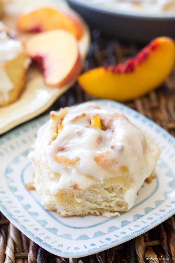 These fluffy cinnamon rolls are filled with fresh peaches, peach jam, and topped with a rich cream cheese glaze. These peaches and cream cinnamon rolls are love at first bite. | www.alattefood.com
