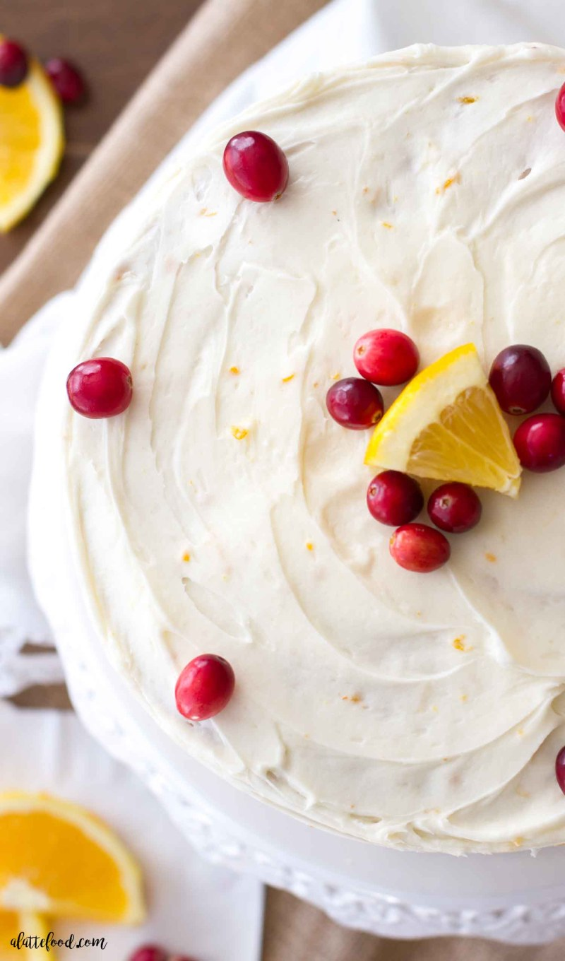 This easy cranberry orange cake is the perfect Christmas dessert! Loaded with cranberries and sweet orange flavor, this homemade cranberry orange cake recipe is a family favorite! Plus, this is topped with an orange cream cheese frosting that is rich, creamy, and ultra-delish!