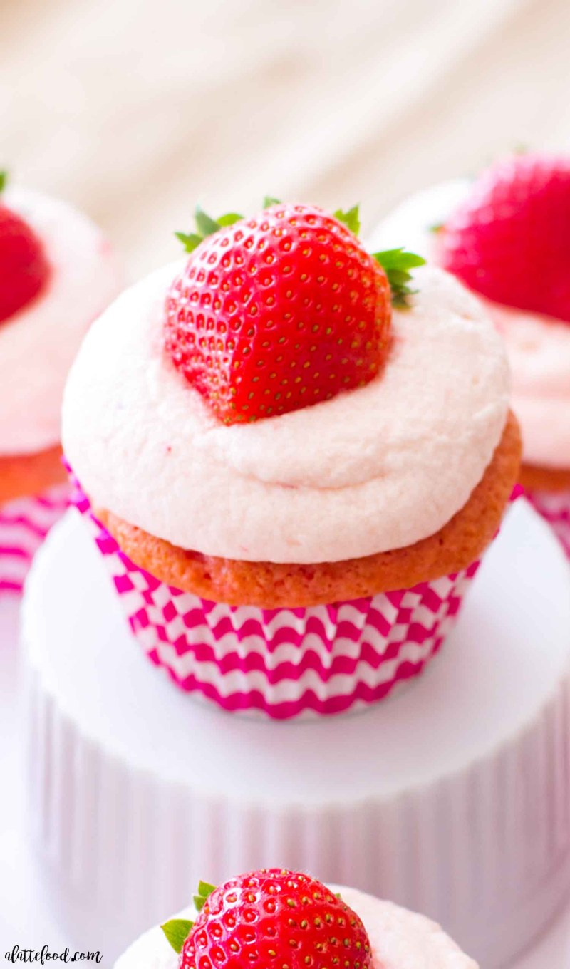 These easy strawberry cupcakes are filled with homemade whipped cream and topped with homemade fresh strawberry frosting! These pretty in pink cupcakes would make the best Valentine's Day dessert, spring dessert, or summer dessert! These strawberries and cream cupcakes begin with a box of white cake mix and strawberry gelatin, making them incredibly simple and entirely flavorful!