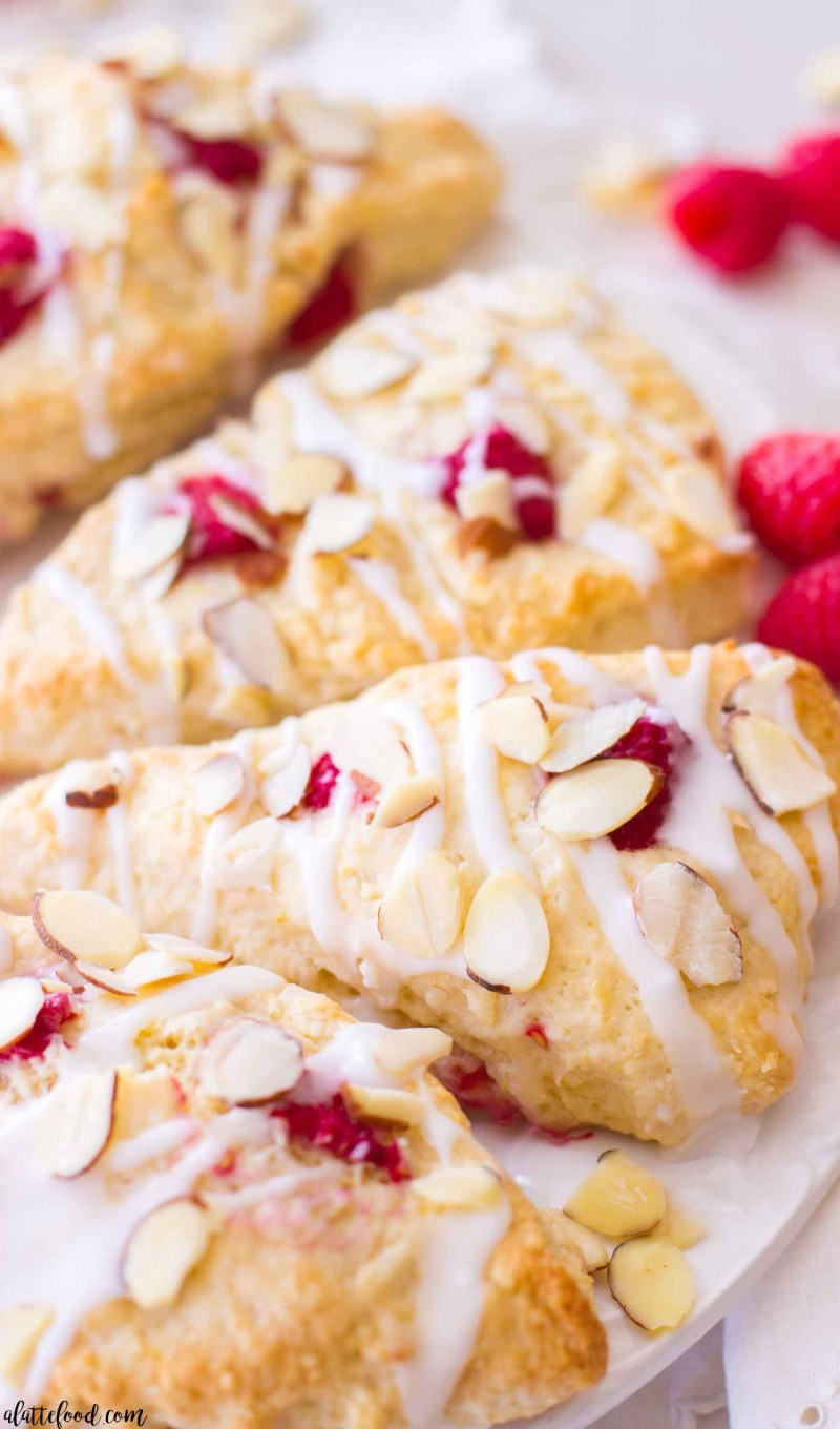 These homemade raspberry almond cream scones are rich, flaky, and full of sweet, fresh raspberries. Plus, these raspberry scones begin with an easy scone recipe that uses simple ingredients, making the recipe come together quickly! We love these raspberry scones, and this raspberry scone recipe makes for a perfect spring or summer breakfast, brunch, or afternoon snack! how to make homemade scones, raspberry scone recipe, the best scones