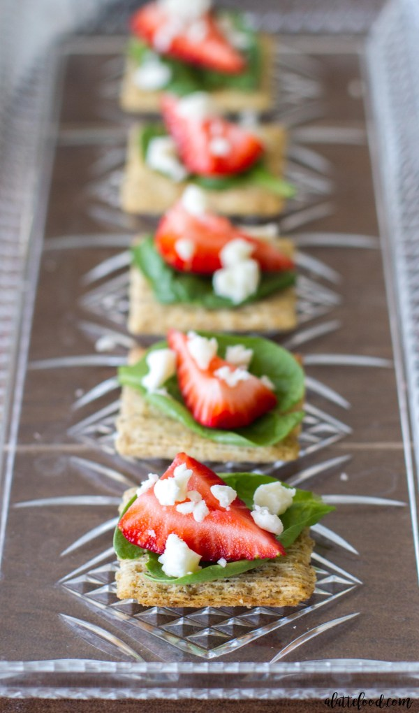 These easy appetizers take only 4-ingredients, but leave a lasting impression! Spinach, strawberries, and feta cheese sit on top of a Cracked Pepper & Olive Oil Triscuit!