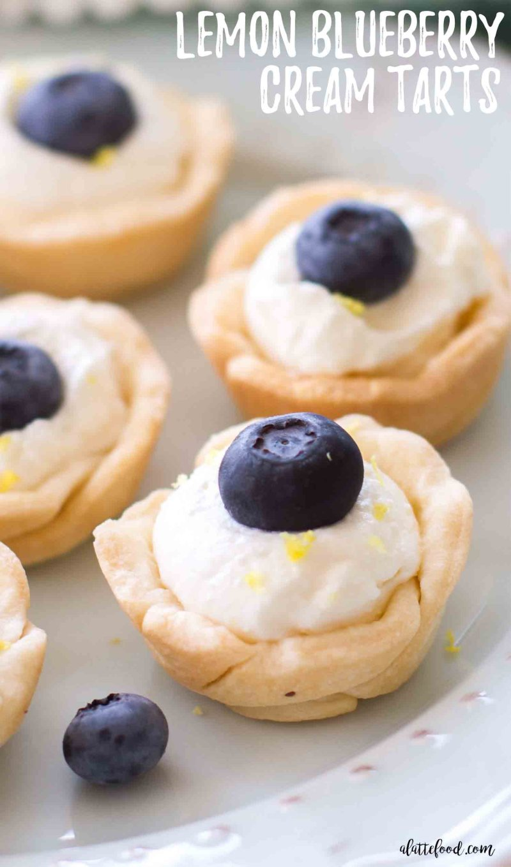 Mini Lemon Blueberry Cream Tarts -- These minilemon blueberry cream tarts are tasty, adorable, and could not be easier! Mini pie crusts are filled with lemon cream and topped with blueberries and lemon zest! Calling all lemon dessert lovers! This lemon blueberry cream tart recipe is a keeper! lemon cream pie, blueberry tarts