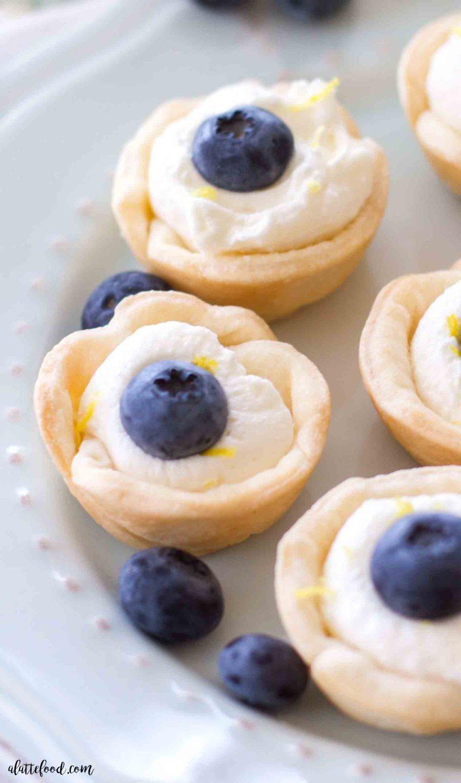 Mini Lemon Blueberry Cream Tarts -- These minilemon blueberry cream tarts are tasty, adorable, and could not be easier! Mini pie crusts are filled with lemon cream and topped with blueberries and lemon zest! Calling all lemon dessert lovers! This lemon blueberry cream tart recipe is a keeper!
