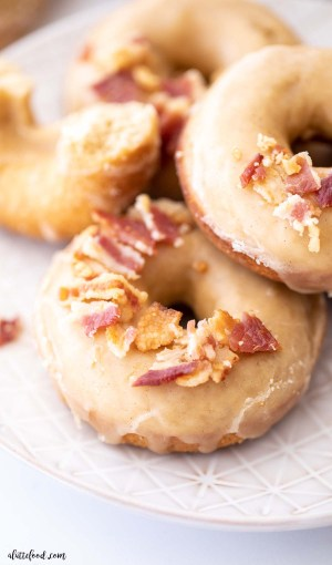 maple glazed donut with crispy bacon crumbles on a gray plate