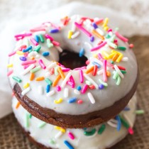 These classic baked chocolate donuts are topped with a homemade vanilla glaze and lots of pretty sprinkles! These are perfect for Valentine's Day, breakfast, and dessert!