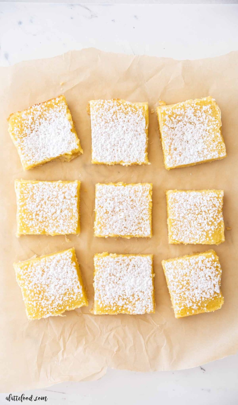 old fashioned lemon squares dusted with powdered sugar on brown parchment paper
