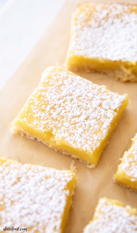 Powdered sugar lemon bars cut into squares on brown parchment paper