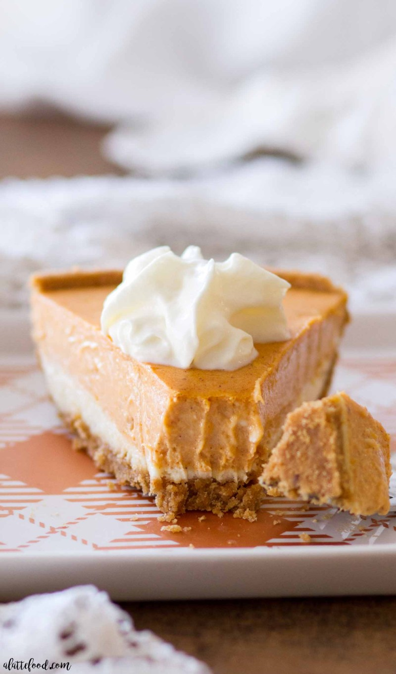 This homemade Pumpkin Cheesecake Recipe is gluten-free! A layer of vanilla cheesecake, a layer of spiced pumpkin cheesecake, and a pinch of whipped cream make this super simple pumpkin cheesecake! It's a holiday dessert favorite around here!