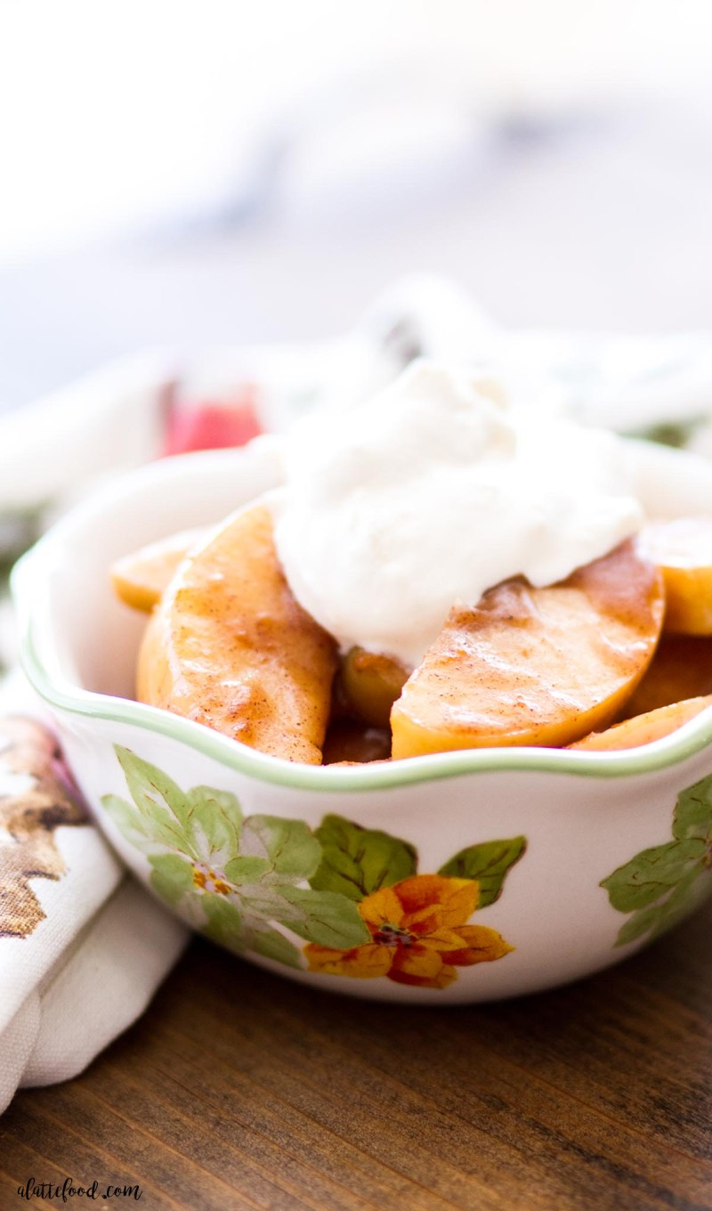 cinnamon spiced apples in a flowered bowl topped with whipped cream