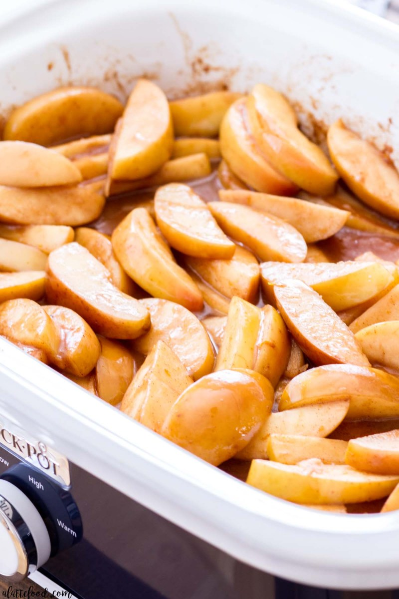 sliced apples cooking in a white and blue slow cooker