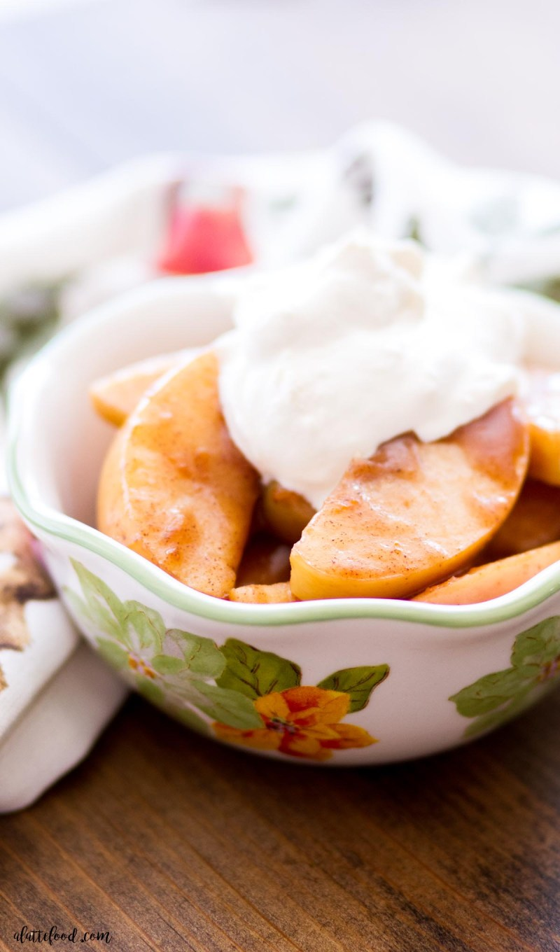 spiced cinnamon apples in a white flowered bowl topped with whipped cream