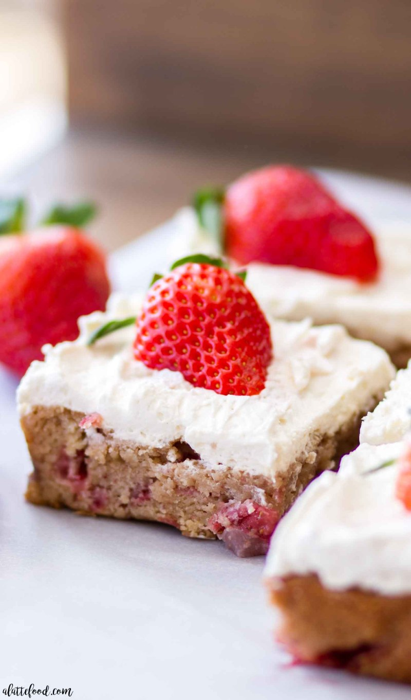 These homemade strawberry blondies are sweet, rich, and the perfect spring dessert! These strawberry blondies are topped with a homemade whipped cream frosting (stabilized whipped cream) and topped with fresh strawberries! This sweet strawberry recipe is great for spring, summer, and Valentine's Day! Plus, a step-by-step video below.