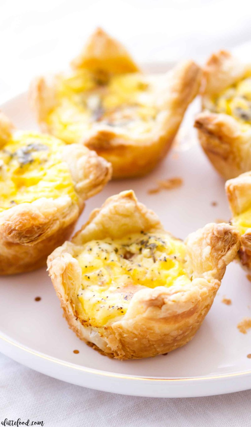 These easy Cheddar and Ham Quiche Cups are made with a puff pastry crust, making these a great quick-and-easy breakfast recipe! Plus, this cheddar and ham quiche recipe can be made ahead of time, stored in the freezer, and baked up whenever you need an on-the-go breakfast!