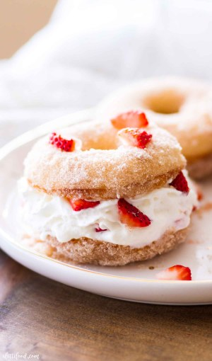strawberry shortcake donut with fresh strawberries on white plate