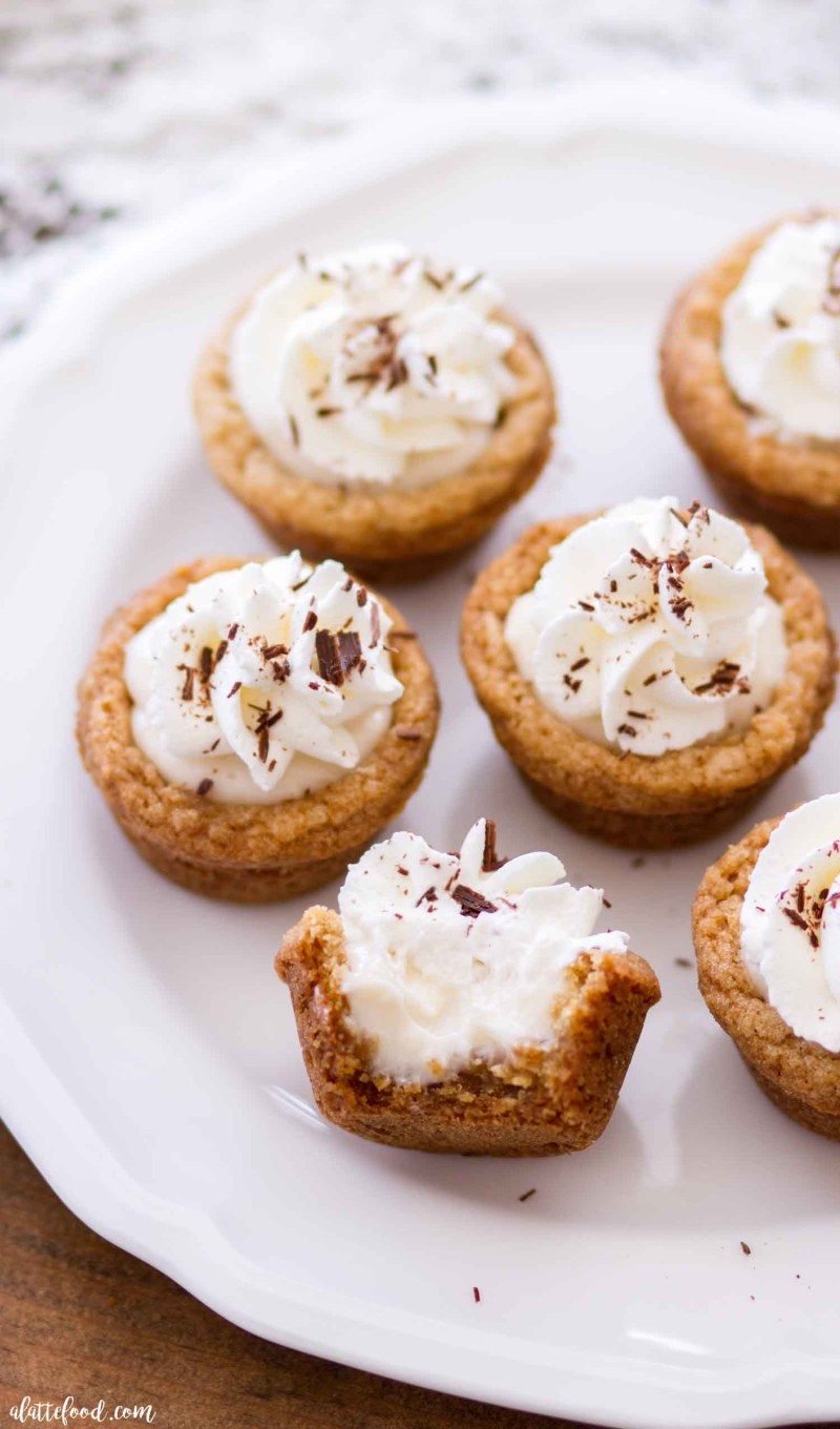 These easy S'mores Cookie Cups have all the flavors of the classic campfire dessert! This S'mores Cookie Cup recipes begins with a graham cracker cookie base, is filled with a sweet mocha marshmallow cream, and topped with whipped cream and chocolate shavings. This might just be your new favorite spring and summer dessert recipe! Plus a step-by-step video down below.