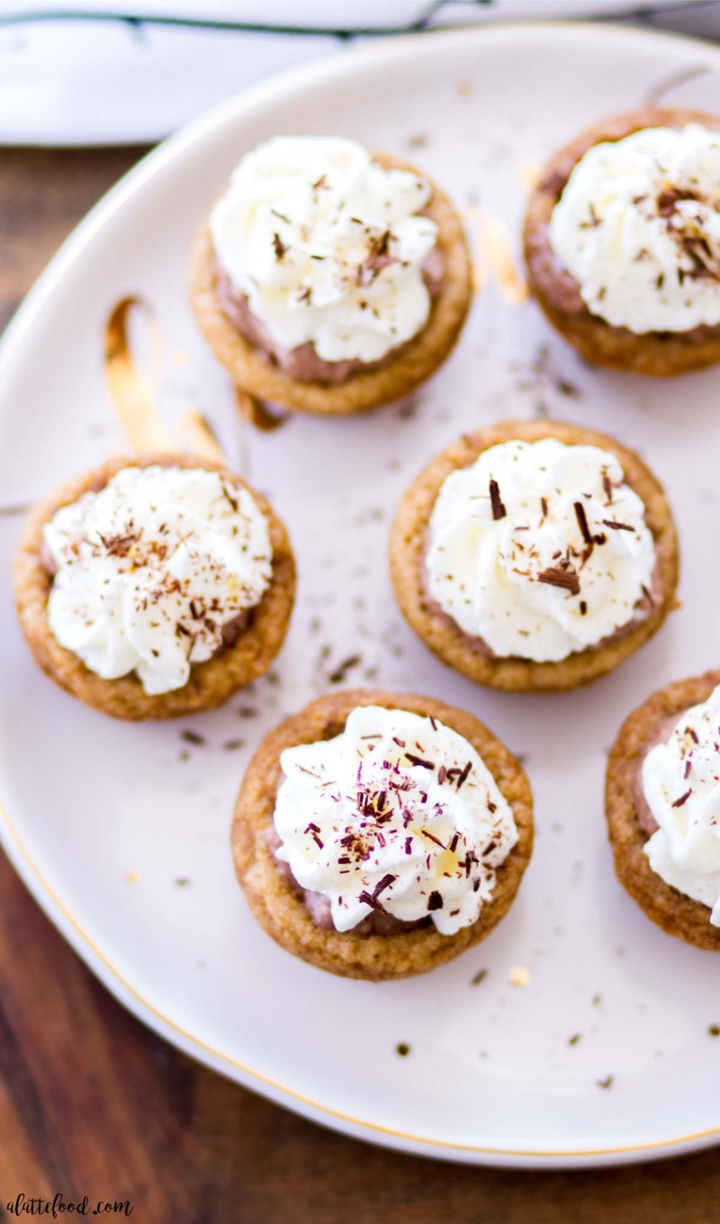 whipped cream topped mini chocolate pies on white plate