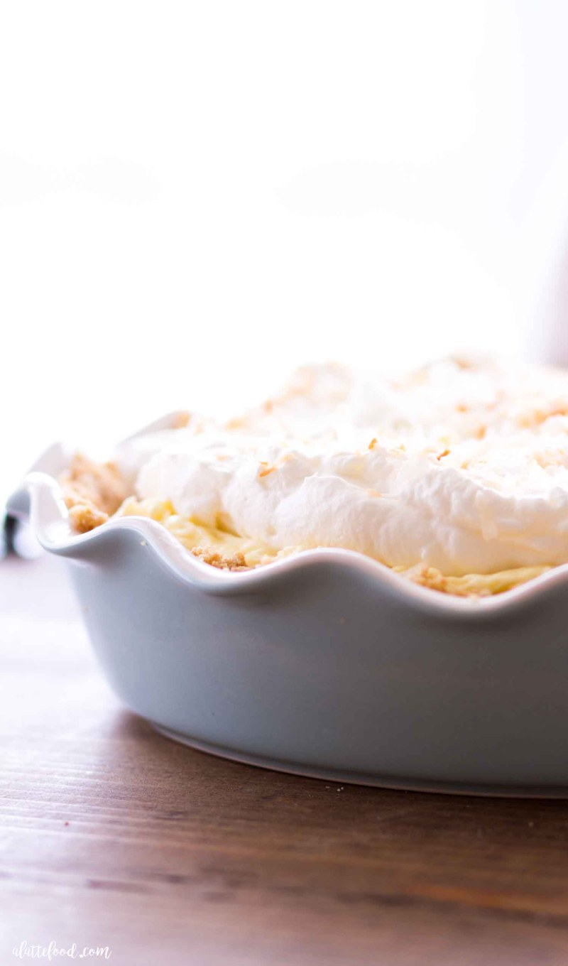 banana cream pie with coconut in blue pie plate