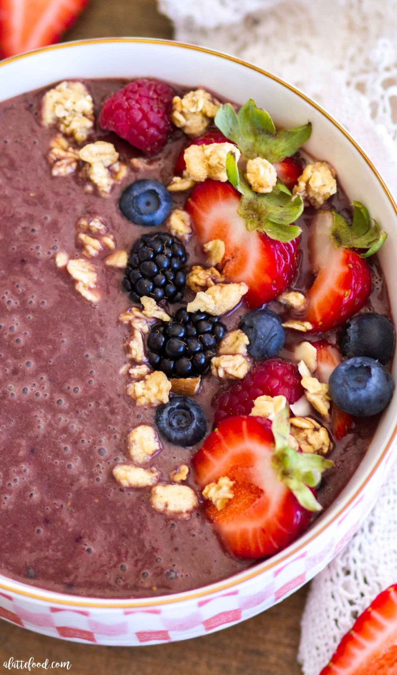 overhead up close photo of acai smoothie bowl in pink bowl