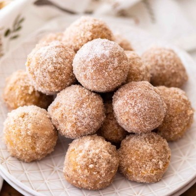 donut holes with pumpkin on stack of plates