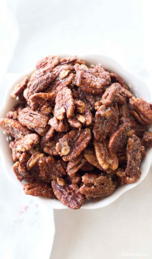 candied maple pecans on white board with white dish towel