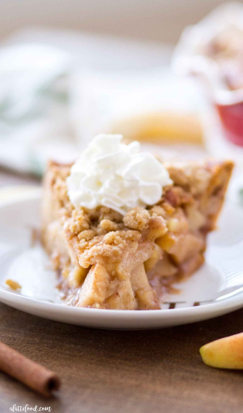This Cinnamon Roll Dutch Apple Pie slice is made with homemade apple pie filling and a cinnamon roll crust.