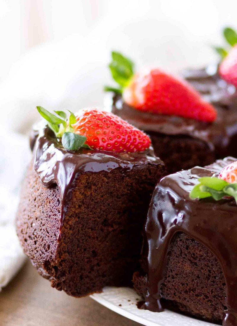 slice of chocolate pound cake with ganache on white plate