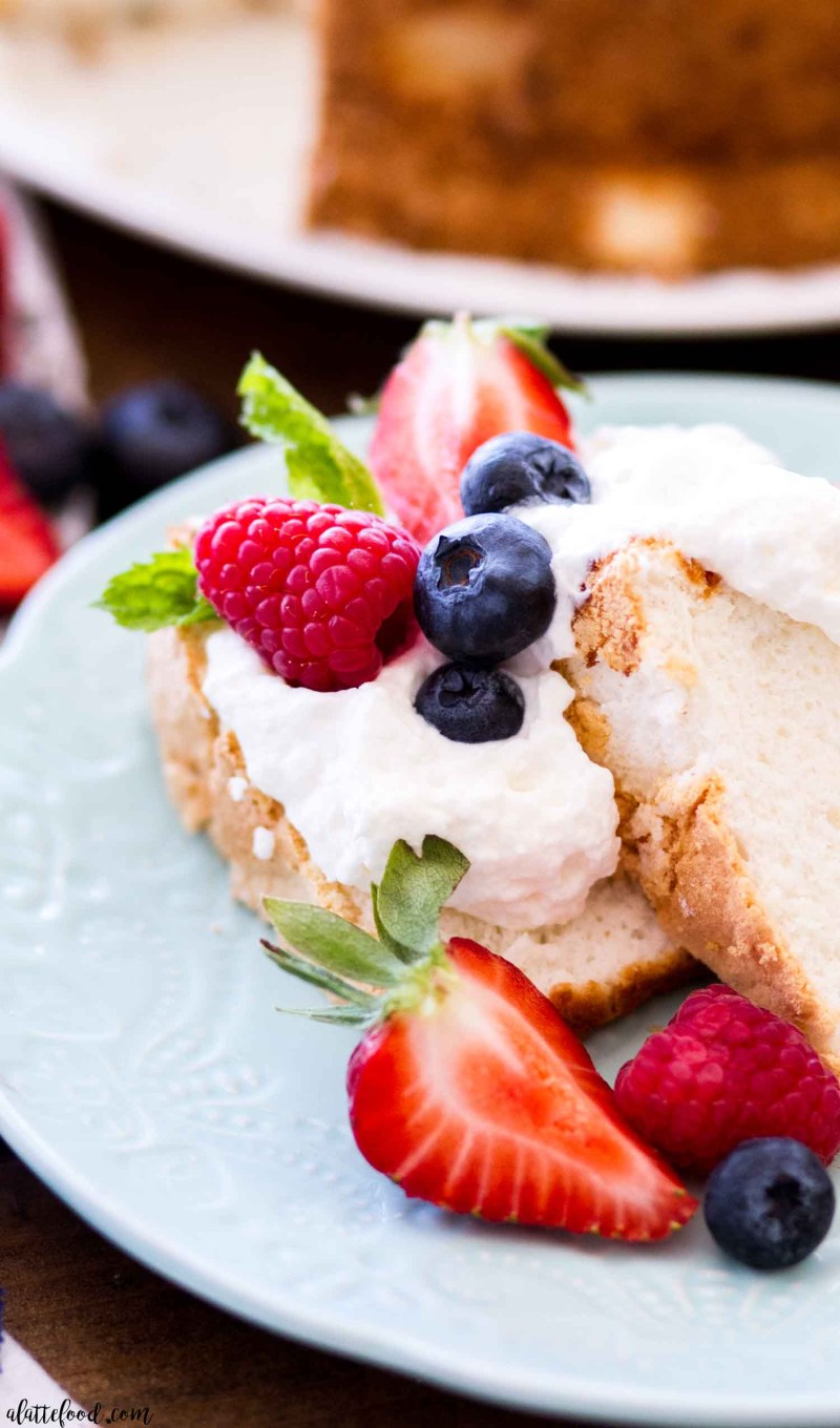 slice of angel food cake with fresh berries and homemade whipped cream