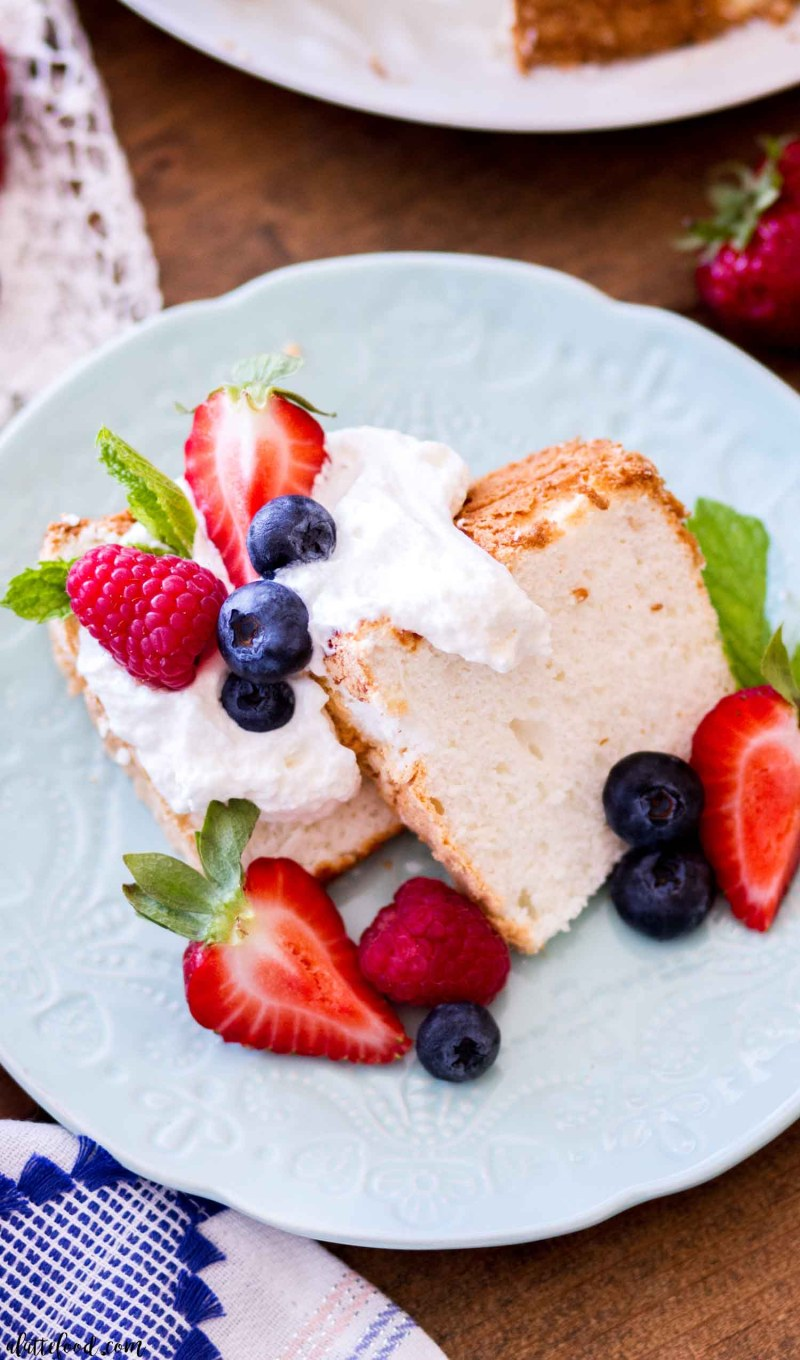 sliced angel food cake on a teal plate with berries and whipped cream