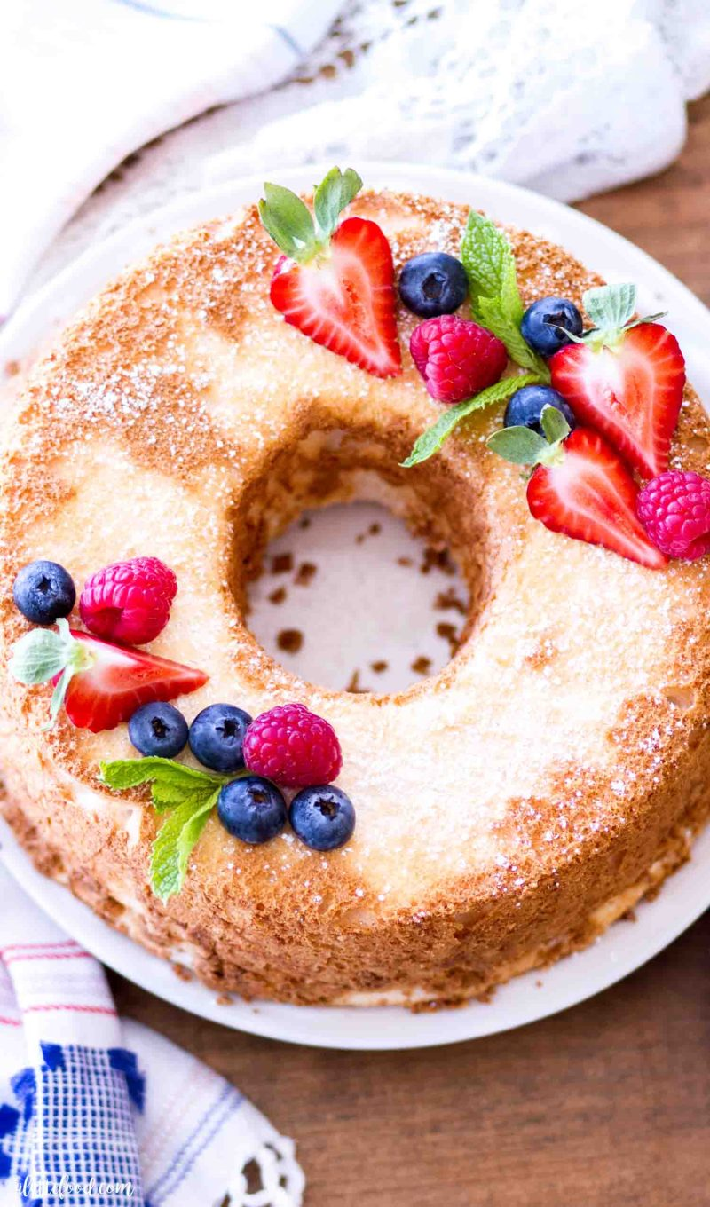 The best angel food cake recipe is topped with fresh berries and powdered sugar