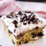 This is the best Oreo Cookies and Cream Poke Cake recipe. A slice of this (on a white plate) is filled with chocolate pudding and topped with whipped cream.
