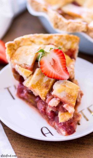 A slice of old fashioned strawberry rhubarb pie (on a white plate) is topped with a homemade lattice crust
