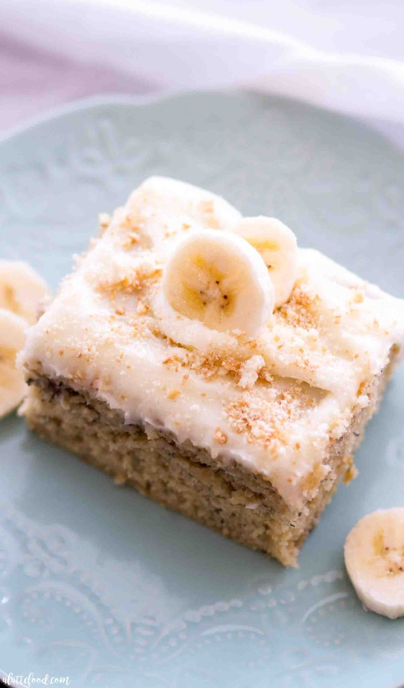 The best banana cake recipe with cream cheese frosting sliced on a teal plate