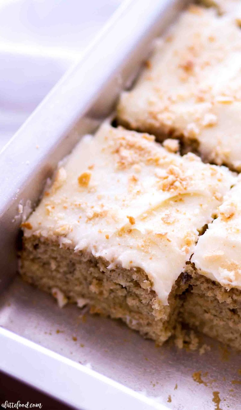 A slice of the best banana cake with cream cheese frosting and nilla wafers.