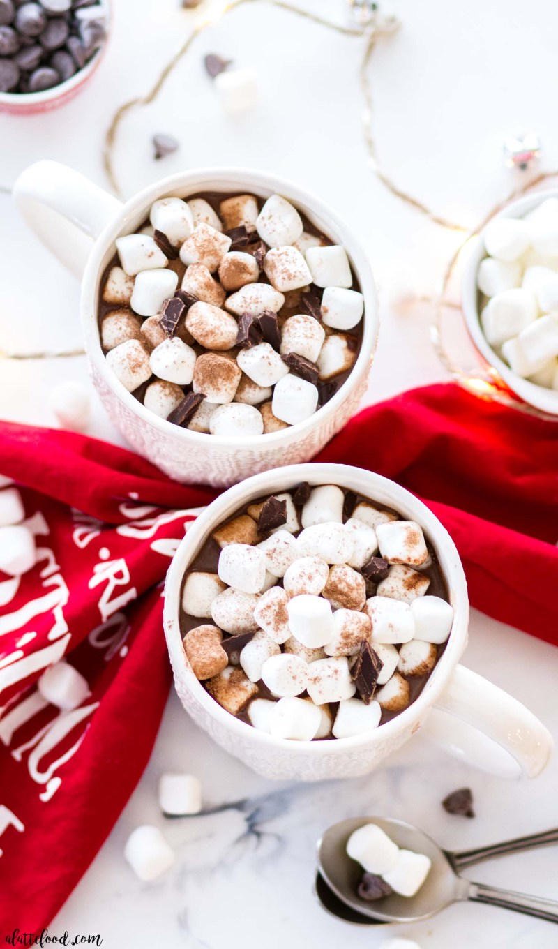 hot chocolate in white mugs with marshmallows and chocolate chips