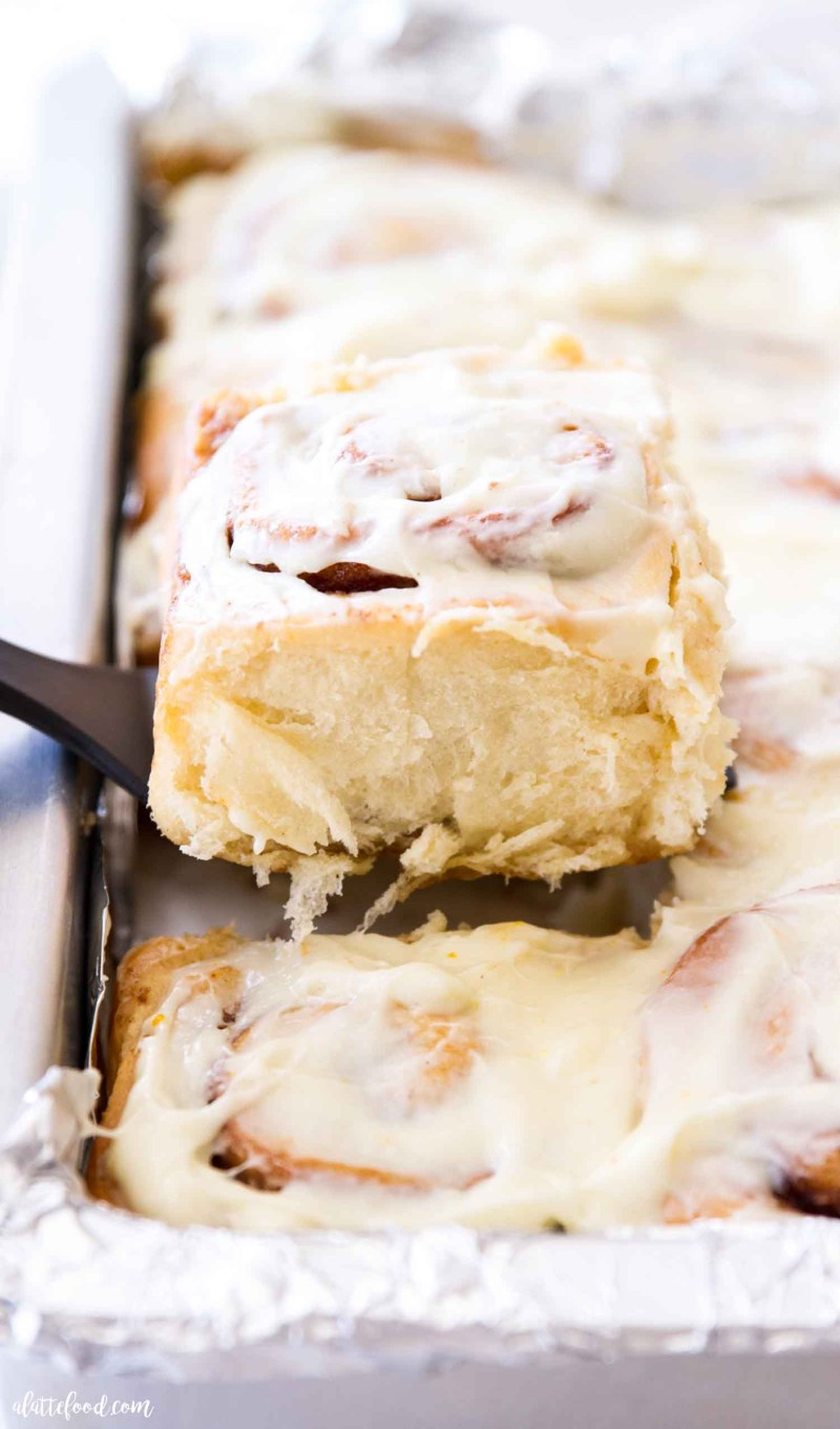 warm gooey cinnamon roll being served with a spatula
