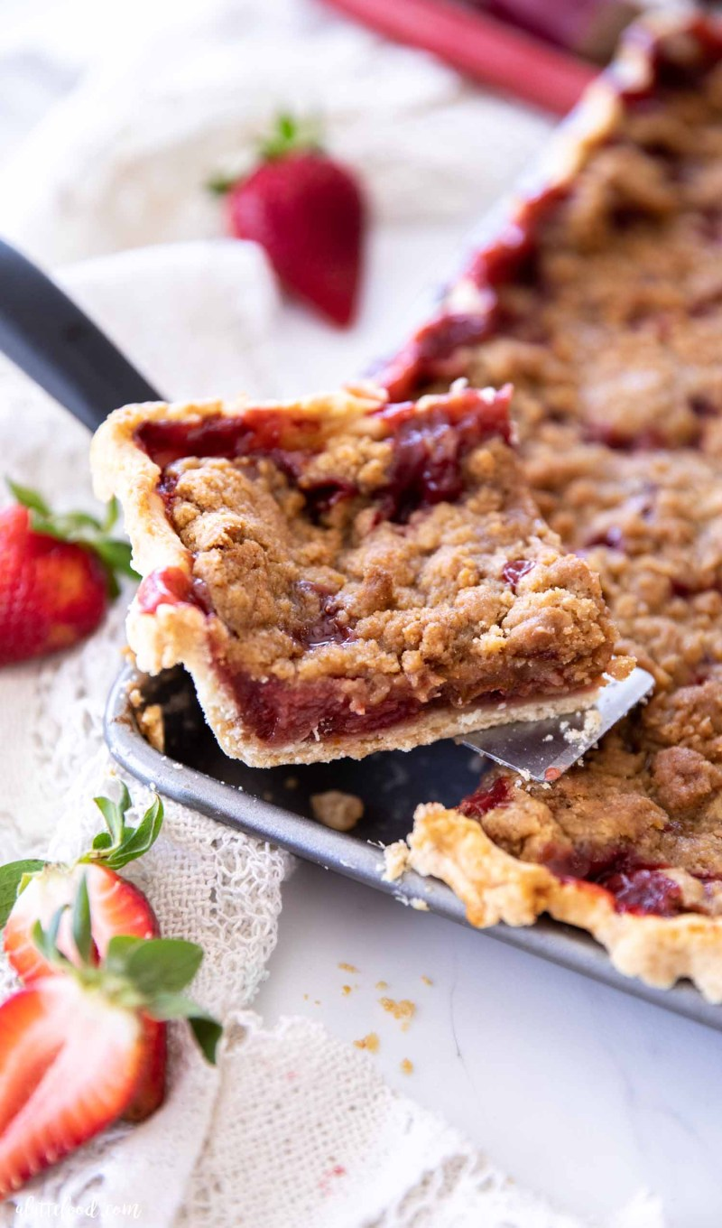 strawberry rhubarb crumb bar slice sitting on pie server