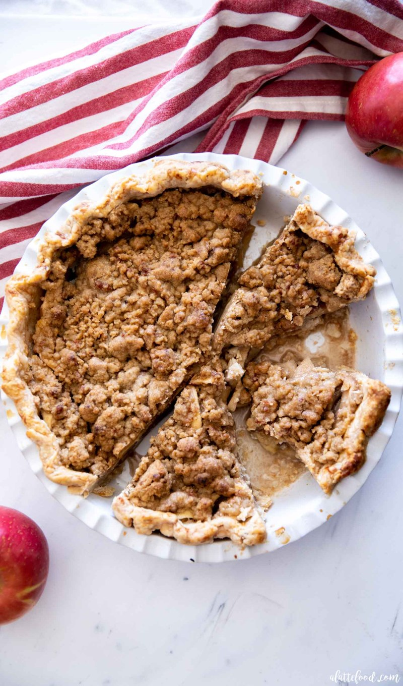 baked apple crumb pie in white pie plate on marble board