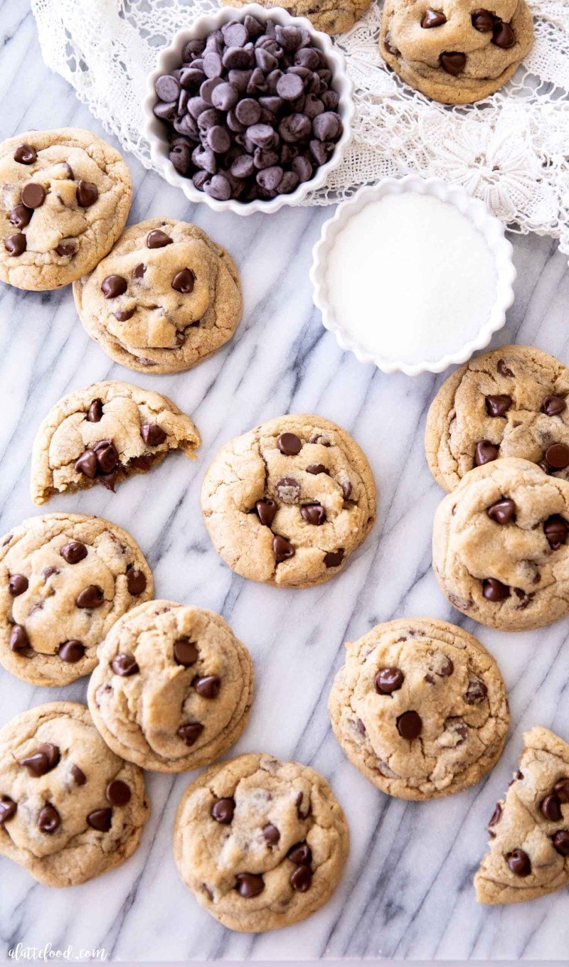 freshly baked chocolate chip cookies on a marble board with white towel