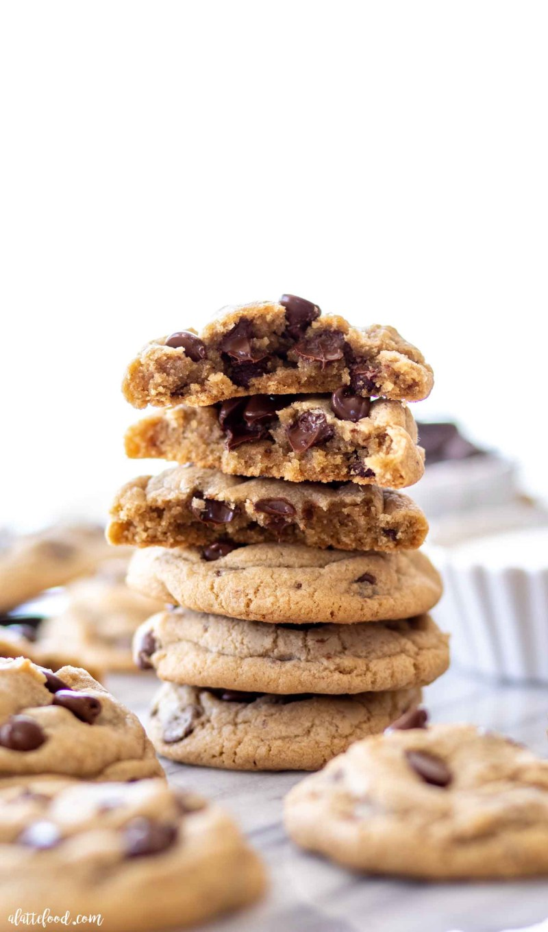 stack of baked chocolate chip cookies with melting chocolate chips on a marble board