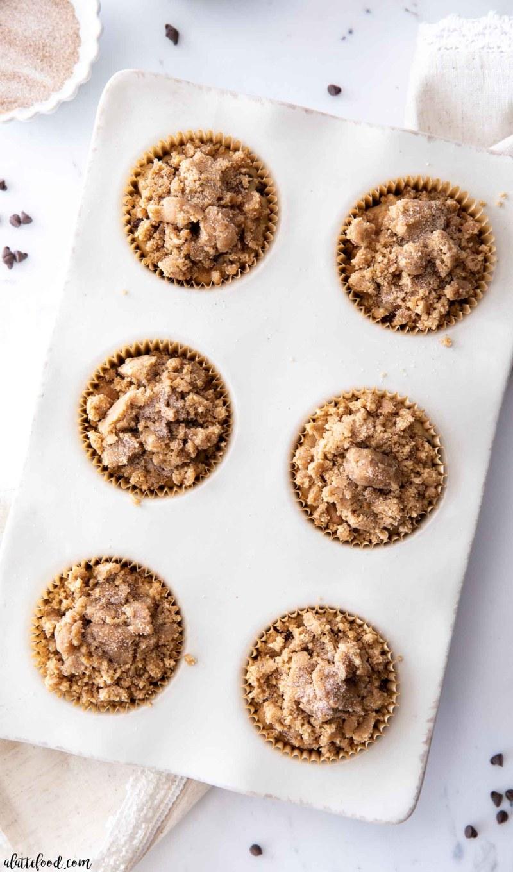 crumb cake chocolate chip muffins unbaked in white muffin tin