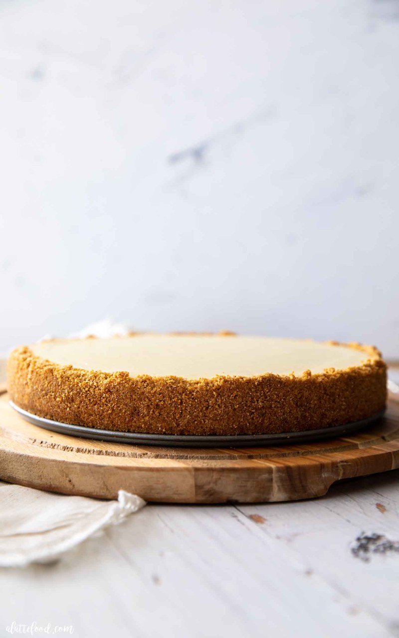 plain cheesecake with graham cracker crumbs on wooden cake plate