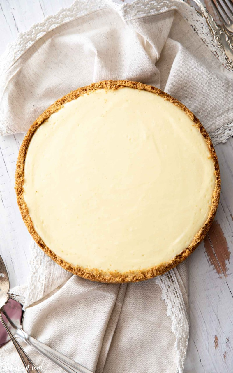 homemade plain cheesecake with a graham cracker crust on white board